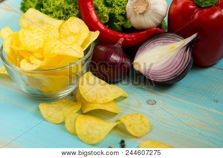 Crispy Potato Chips In A Glass Bowl With Chili Peper, Garlic, Salad And Onions On Old Blue Wooden Ba