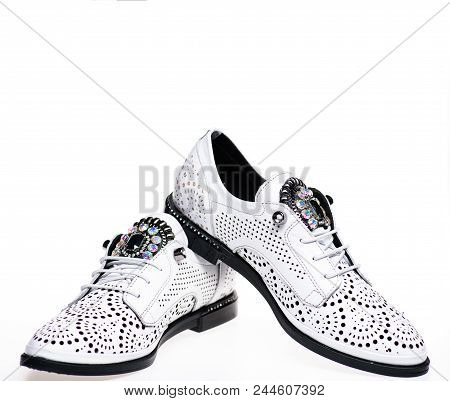 Pair of fashionable comfortable oxfords shoes. Modern shoes concept. Footwear for women on flat sole with perforation and rhinestones. Shoes made out of white leather on white background, isolated. poster