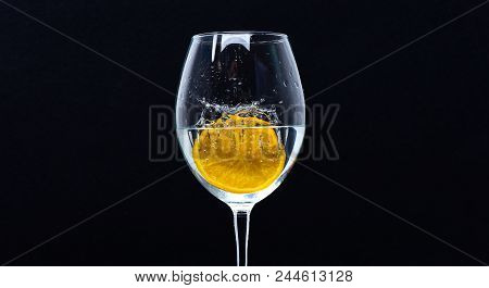 Wineglass Filling With Water With Splashes On Black Background. Refreshing Drink Concept. Glass With