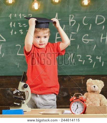 Kid Boy In Graduate Cap Ready To Go To School, Chalkboard On Background. Child, Pupil On Smiling Fac