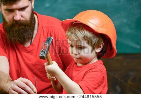 Boy, Child Busy In Protective Helmet Learning To Use Hammer With Dad. Fatherhood Concept. Father Wit