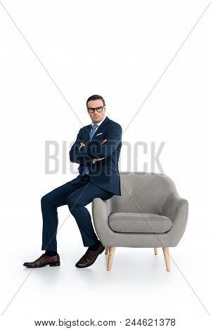 Full Length View Of Confident Businessman In Eyeglasses Sitting With Crossed Arms And Looking At Cam