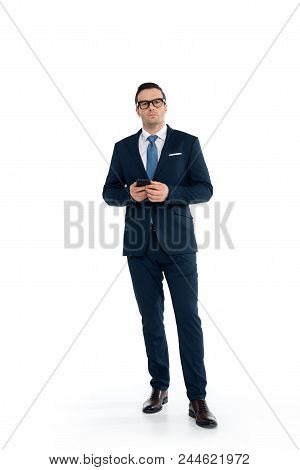 Full Length View Of Confident Buisnessman In Eyeglasses Holding Smartphone And Looking At Camera Iso