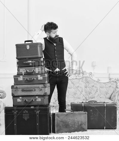 Baggage and relocation concept. Macho elegant on tired face, exhausted at end of packing, leans on pile of vintage suitcases. Man with beard and mustache packed luggage, white interior background poster