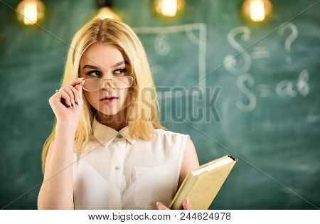 Attractive lecturer concept. Woman with book starts lesson, gazes at audience while taking off eyeglasses. Teacher looks confident in eyeglasses, stand in classroom, chalkboard on background. poster
