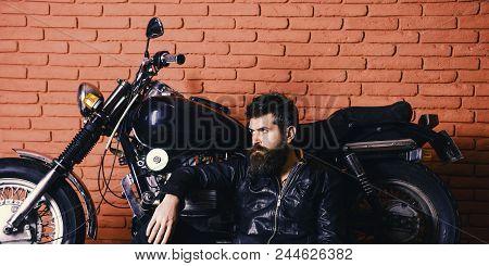 Brutal Biker Concept. Hipster, Brutal Biker On Pensive Face In Leather Jacket Sit On Floor Near Moto