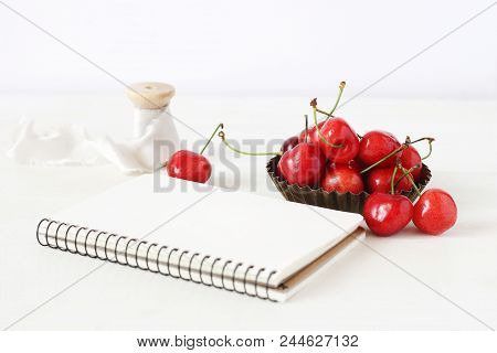 Feminine Still Life Composition. Sweet Red Cherry Fruit In Little Metal Bowl, Blank Notebook And Spo