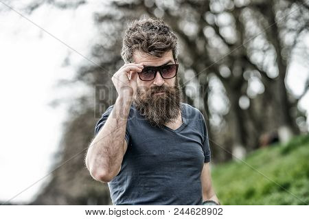 Guy Looks Cool With Stylish Sunglasses. Man With Beard And Mustache Wears Sunglasses, Defocused Back