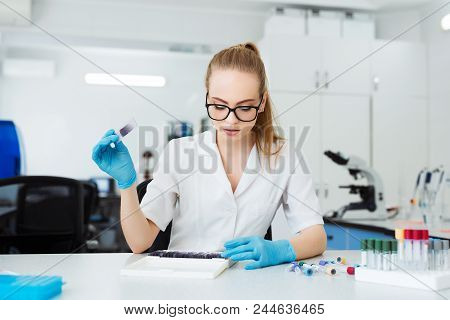 Scientist Analyzing Microscope Slide At Laboratory. Female Working In Laboratory With Microscope. Re