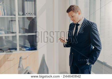 Business, Office, People And Technology Concept. Successful Businessman Holds Smart Phone, Reads Tex