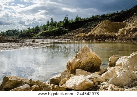 Landscape Pond In A Limestone Quarry, Yellow, Sandy, Pond, Forest In The Distance