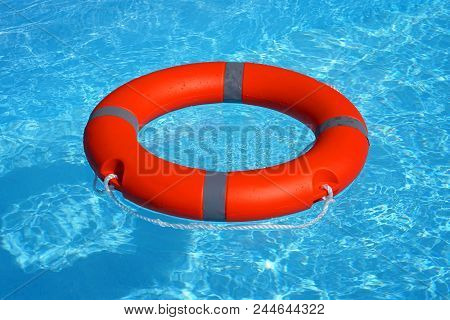 Red Lifebuoy Pool Ring Float On Blue Water. Life Ring Floating On Top Of Sunny Blue Water. Life Ring
