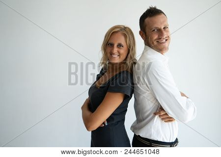Cheerful Confident Business Couple Standing Back To Back And Looking At Camera. Positive Successful