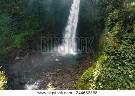 Waterfall In The Rain Forest. People Are Swimming In The Waterfall. Waterfall Beauty Of Nature.
