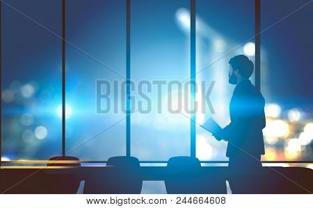 Lonely Businessman With Papers Standing In A Modern Panoramic Windows Office. A Night Cityscape Back