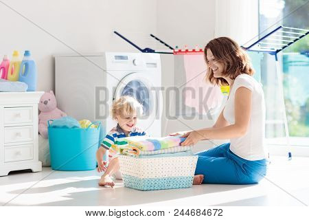Laundry room with washing machine or tumble dryer. Modern household devices in white sunny home. Clean washed clothes on drying rack. Liquid washing detergent in plastic bottle and fabric softener. poster