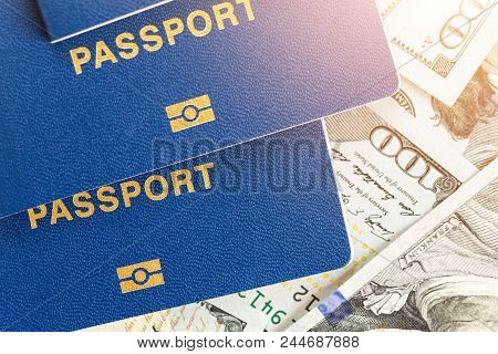 Three Biometrical International Passports Over Money Background. Blue Travel Documents Lying On Us O