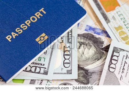 Biometrical International Passport Over Money Background. Blue Travel Documents Lying On Us One Hund