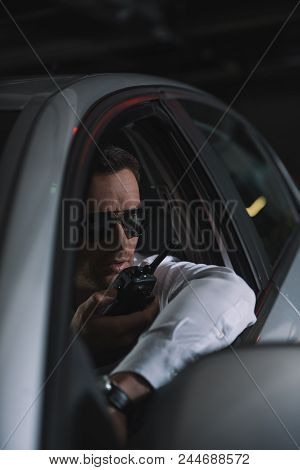 male undercover agent in sunglasses doing surveillance and using talkie walkie in car poster