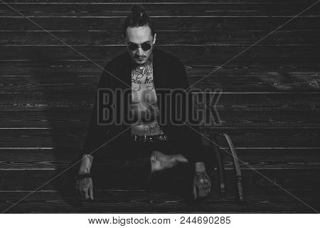 Reincarnation And Rebirth. Man With Tattooed Torso In Black Clothes Sitting In Meditation Pose With