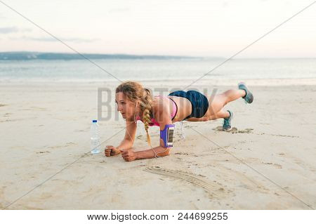young sportswoman in earphones with smartphone in running armband case and bottle of water doing plank on sandy beach poster