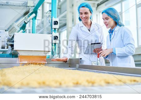 Waist Up Portrait Of  Two Young Female Workers Wearing Lab Coats Standing By  Conveyor Line With Mac