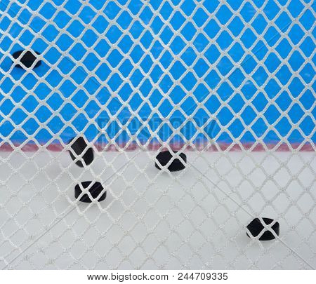 Closeup View Of Nylon Netting. Color Patterns In The Background, These Are Logos On Hockey Ice. The