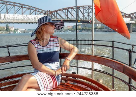 A Pretty Smiling Elegant Woman In A Hat, Middle Aged, Sitting On A Ferry Bench, Enjoying A Sightseei