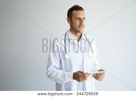 Pensive Doctor Analyzing Medical History And Thinking Over Treatment. Handsome Male Practitioner Hol