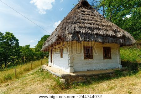 Old Natural Style Wooden Cottage With Straw Roof In Woodland Landscape
