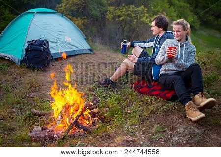 Young Happy Couple Travelers Hiking In Forest. Smiling Couple Resting Enjoying A Break During Hike V
