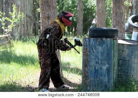 A Teenager Girl Or Boy In A Spotted Protective Suit And Wearing A Red Protective Mask Plays Paintbal