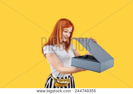What is inside. Pleasant excited woman holding a box while being curious what is inside of it poster