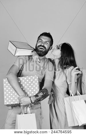 Money And Shopping Concept. Couple In Love Holds Shopping Bags, Hugs And Kisses On Grey Background.