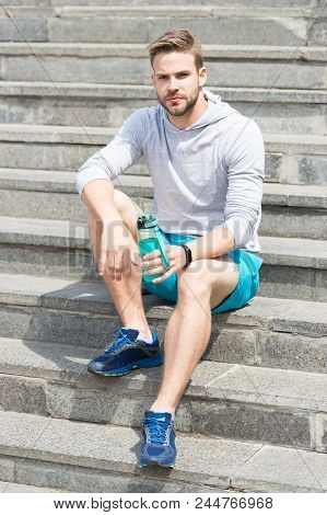 Working Out On Stairs. Man Athletic Appearance Holds Water Bottle. Man Athlete Sport Clothes Refresh