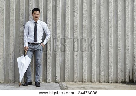 Asian Business Man Leaning On A Wall