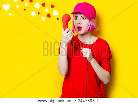 Portrait Of Beautiful Surprised Young Woman With Red Handset On The Wonderful Yellow Studio Backgrou