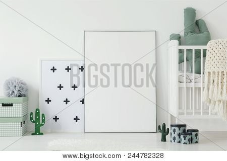 Mockup Of White Empty Poster Next To Cradle In Kid's Room Interior With Cactus Motif. Real Photo