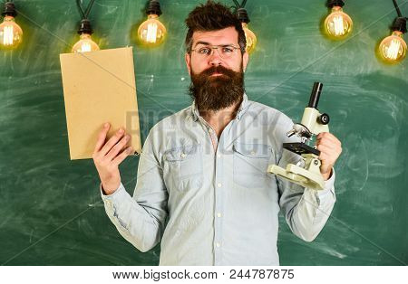 Teacher In Eyeglasses Holds Book And Microscope. Man With Beard And Mustache On Strict Face In Class