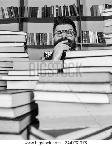 Teacher Or Student With Beard Wears Eyeglasses, Sits At Table With Books, Defocused. Man On Thoughtf