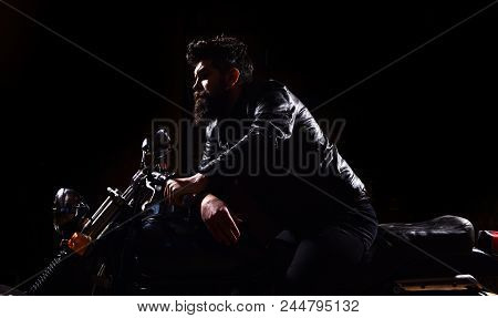 Masculinity concept. Macho, brutal biker in leather jacket riding motorcycle at night time, copy space. Man with beard, biker in leather jacket sitting on motor bike in darkness, black background. poster