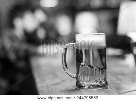 Glass With Beer On Bar Counter, Table, Visitor On Background, Defocused. Glass With Fresh Lager Draf