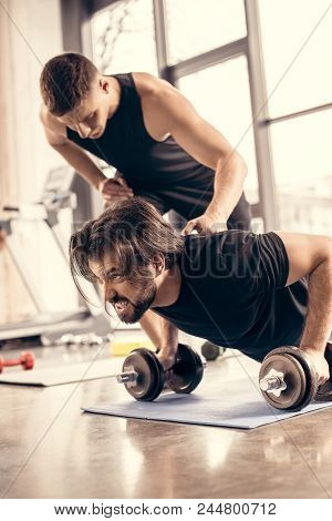 Trainer Pushing Sportsman Doing Push Ups On Dumbbells In Gym
