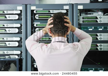 it business man in network server room have problems and looking for  disaster situation  solution