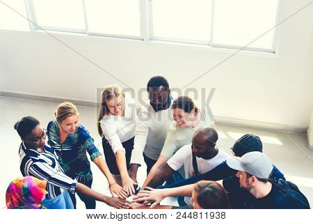 Diverse people joining together as a team