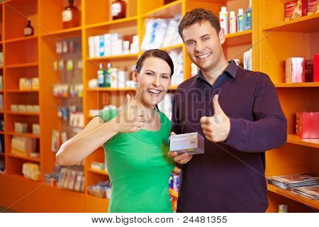 Couple In Pharmacy Holding Thumbs Up