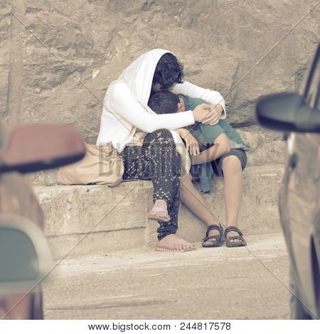 OSTROG MONASTERY, MONTENEGRO - JULY 19, 2017: mother consoling the young son with a hug