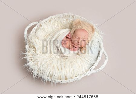 Newborn baby in funny bonnet napping in basket