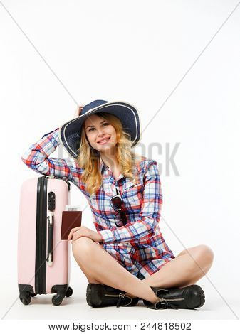Image of woman in hat with passport sitting near suitcase