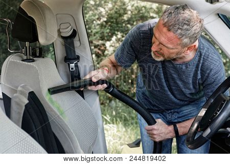 Man hoovering a seat inside a car cabin, visible dirt. Cleaning car with vacuum cleaner.
